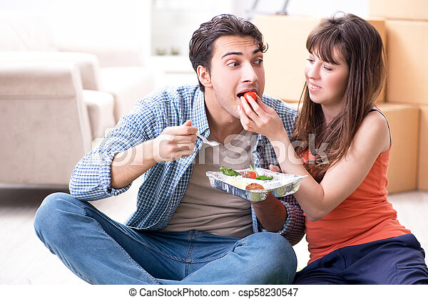 Young family eating food in new apartment after moving in - csp58230547