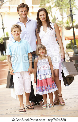 Young Family Enjoying Shopping Trip Together - csp7424529
