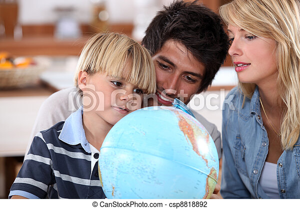 Young family looking at a globe - csp8818892