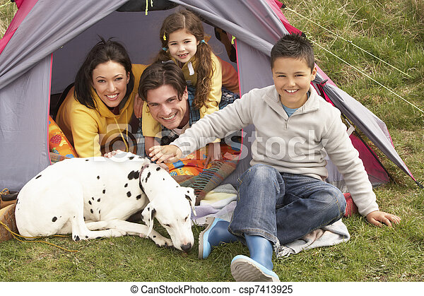 Young Family With Dog Relaxing Inside Tent On Camping Holiday - csp7413925