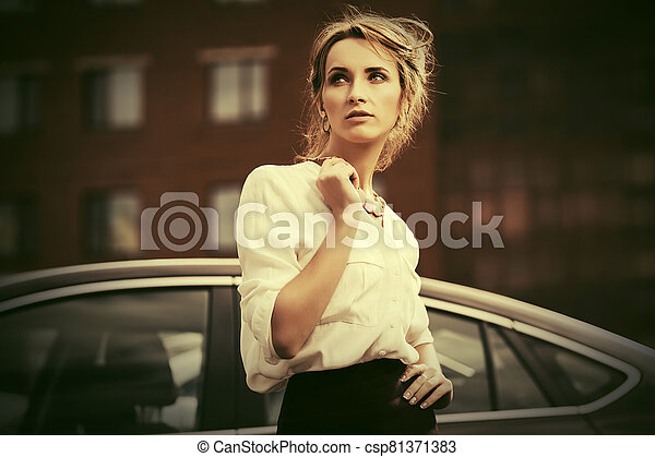 Young fashion business woman in white shirt next to her car - csp81371383