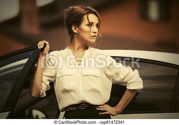Young fashion business woman in white shirt next to her car - csp81472341