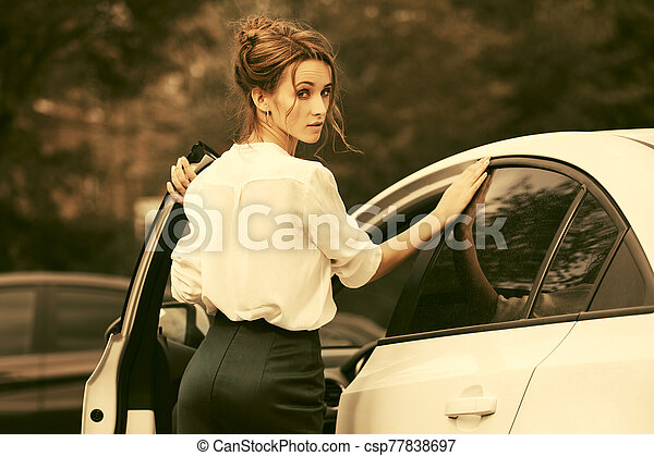 Young fashion business woman in white shirt next to her car - csp77838697