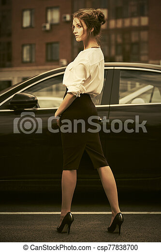 Young fashion business woman in white shirt next to her car - csp77838700