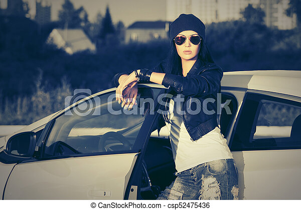 Young fashion woman in sunglasses standing next to her car - csp52475436