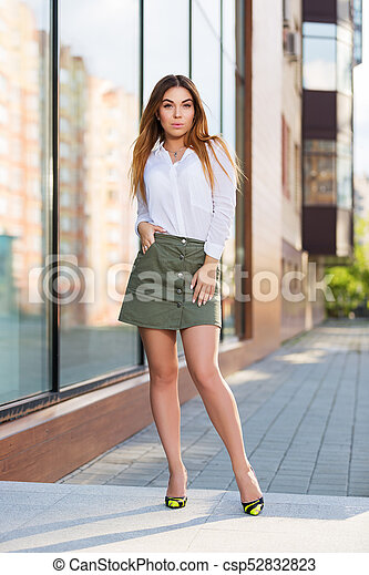 ebdb2e669018 Young fashion woman in white blouse and short skirt in a city street -  csp52832823