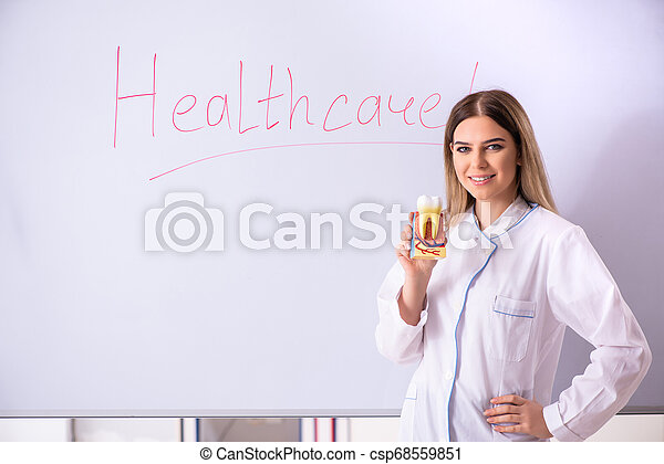 Young female doctor standing in front of the white board - csp68559851