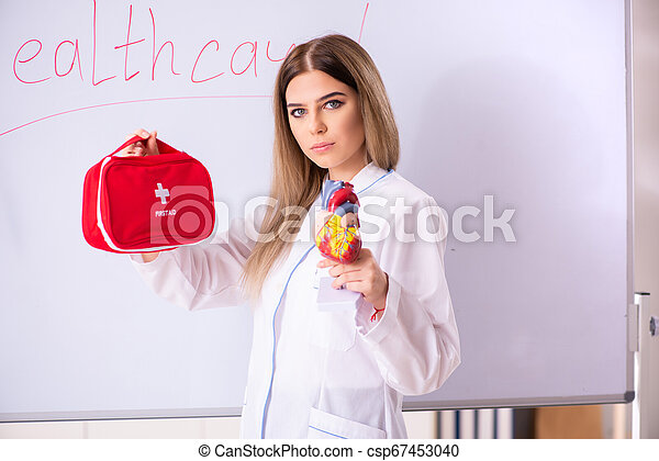 Young female doctor standing in front of the white board - csp67453040