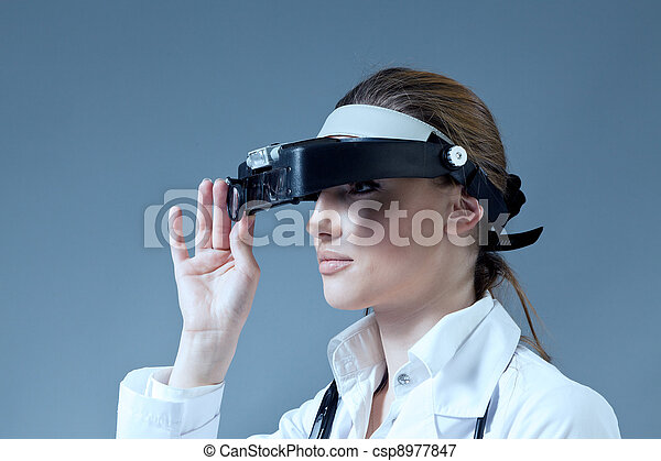 Young female doctor wearing magnifying glass equipment on her had. Medical / pharmaceutical research concept. Healthcare collection. - csp8977847