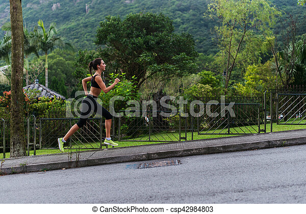 Young fit woman doing cardio exercise, listening to music, running outdoors with green mountain landscape in the background - csp42984803