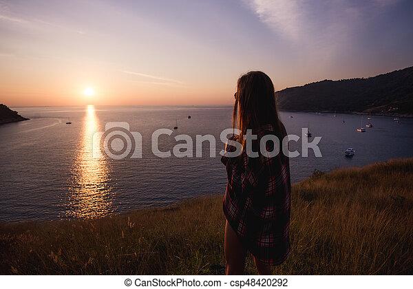 young freedom woman enjoy ocean sunset on mountain peak - csp48420292