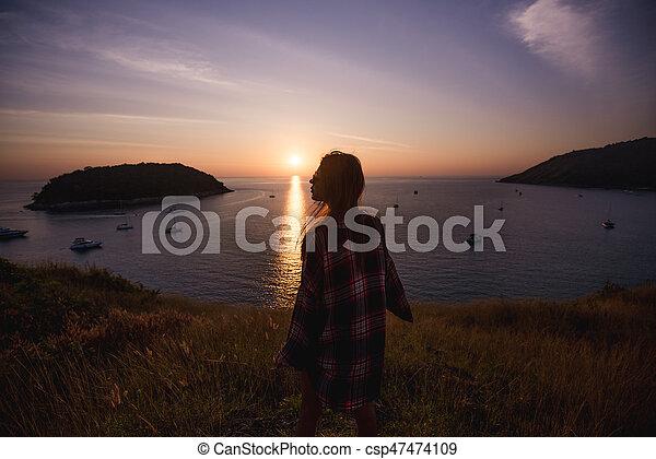 young freedom woman enjoy ocean sunset on mountain peak - csp47474109