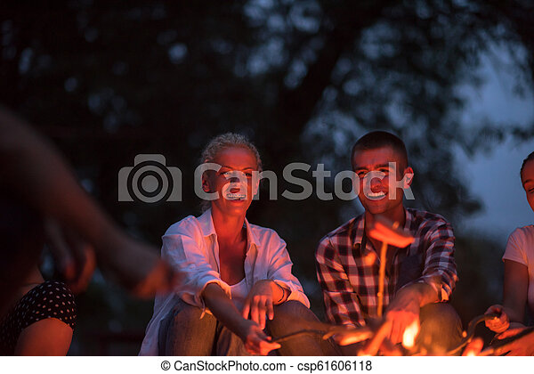 young friends relaxing around campfire - csp61606118