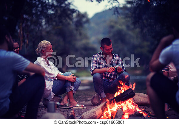 young friends relaxing around campfire - csp61605861