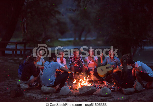 young friends relaxing around campfire - csp61606368