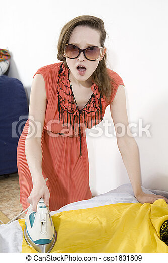 young furious woman ironing yellow dress - csp1831809
