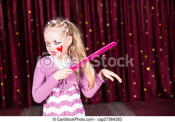 Young Girl Clown Brushing Hair with Large Comb - csp27364383