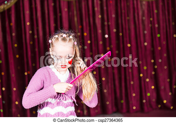Young Girl Clown Brushing Hair with Large Comb - csp27364365