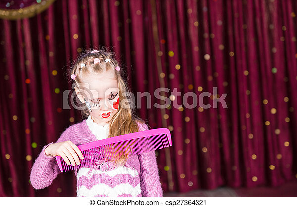 Young Girl Clown Brushing Hair with Large Comb - csp27364321