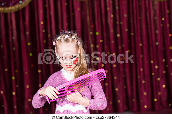 Young Girl Clown Brushing Hair with Large Comb - csp27364344