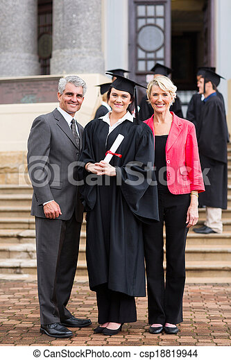 young girl graduate standing with parents - csp18819944