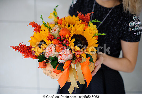 58d19a23b3 Young girl holding a bouquet of sunflowers and other flowers.
