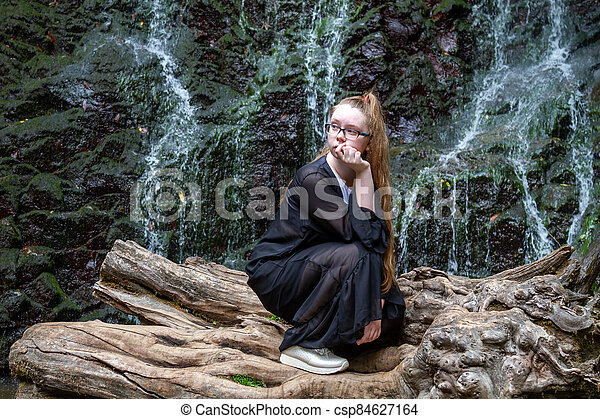Young girl in black posing squatting on a large dry tree against the background of a mountain waterfall - csp84627164