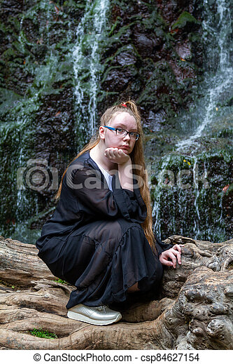 Young girl in black posing squatting on a large dry tree against the background of a mountain waterfall - csp84627154