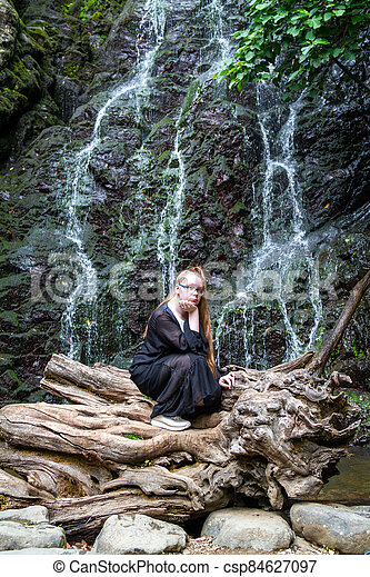 Young girl in black posing squatting on a large dry tree against the background of a mountain waterfall - csp84627097