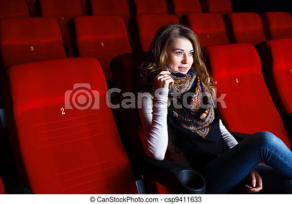 Young girl in cinema watching movie - csp9411633