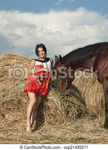 young girl in dress with horse near hay - csp21435571