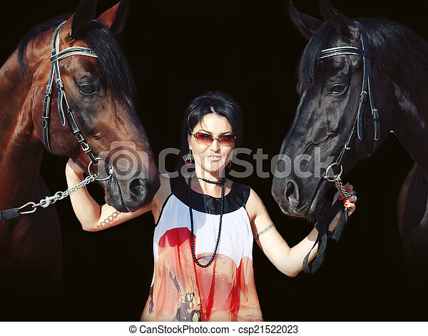 young girl in dress with two horses at black background - csp21522023