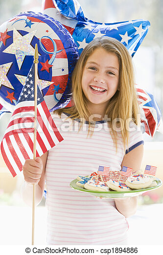 Young girl outdoors on fourth of July with flag and cookies smil - csp1894886