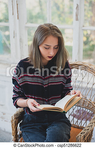 young girl reading a book in a wicker chair. Autumn mood. - csp51286622