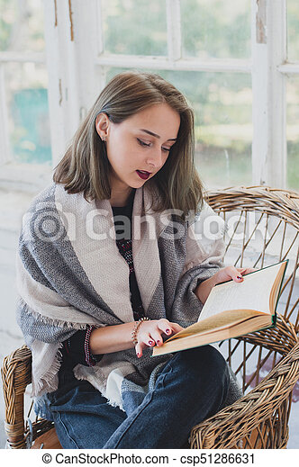 young girl reading a book in a wicker chair. Autumn mood. - csp51286631