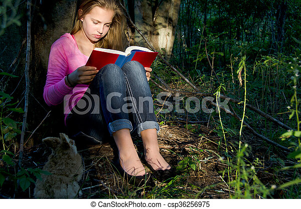 young girl reading book in forest - csp36256975