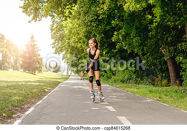 Young girl roller skating in park - csp84615268