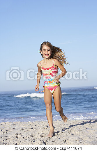 young girl running along sandy beach