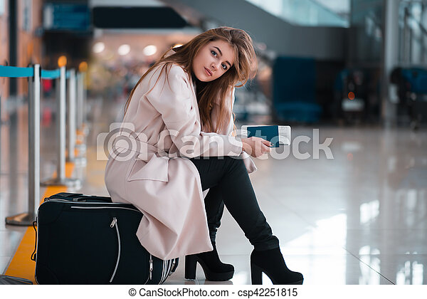 Young girl sits on a suitcase in airport. - csp42251815