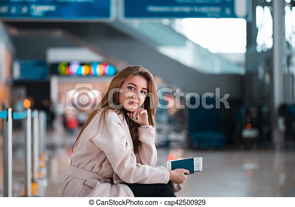 Young girl sits on a suitcase in airport. - csp42500929