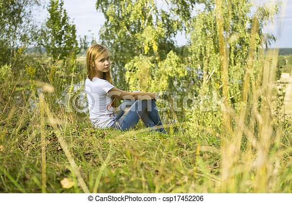 young girl sitting in the grass - csp17452206