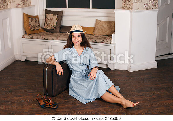Young girl sitting on the floor with a suitcase. - csp42725880
