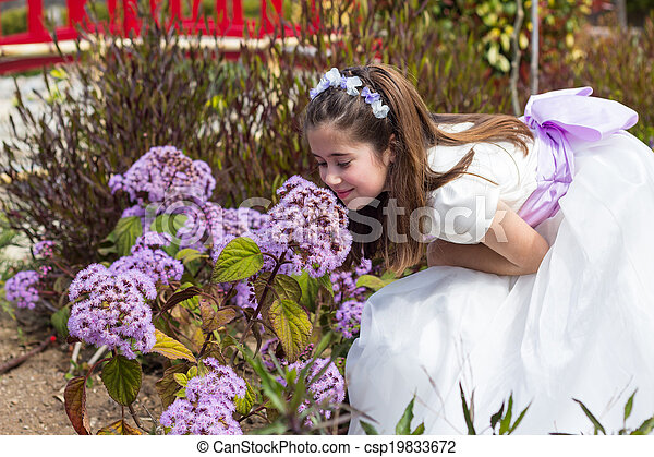 Young girl smelling flowers - csp19833672