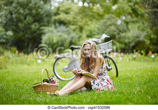 Young girl with eading a book outdoors - csp41532586