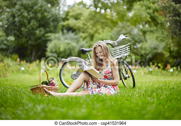 Young girl with eading a book outdoors - csp41531964