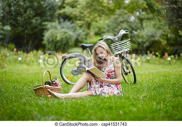 Young girl with eading a book outdoors - csp41531743