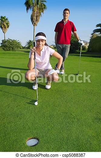 young golf woman looking and aiming the hole - csp5088387