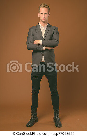 Young handsome blonde businessman against brown background - csp77063550