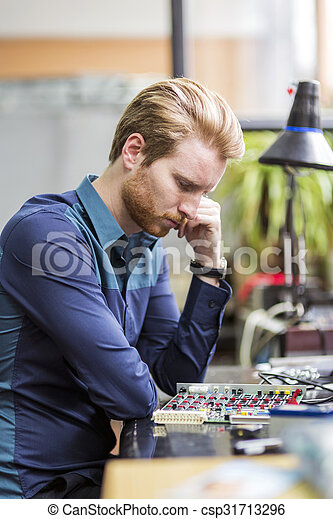 Young handsome man thinking while soldering a circuit board - csp31713296