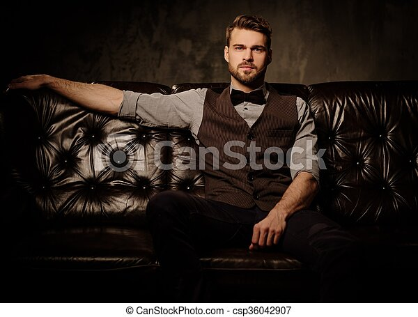 Young handsome old-fashioned bearded man sitting on comfortable leather sofa on dark background.  - csp36042907